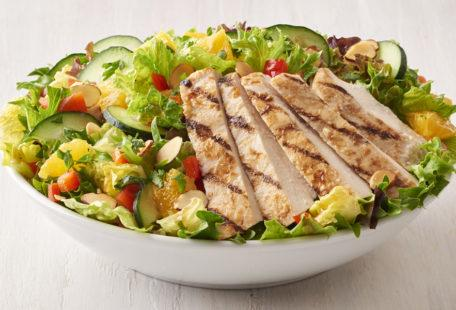 Asian Chicken Salad with oranges, cucumbers, red bell pepper, almonds in a bowl