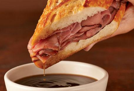 Sourdough French Dip with roast beef on a sourdough baguette dipped in au jus