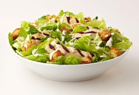 Caesar Salad with chicken, sourdough croutons and Parmesan cheese in a bowl