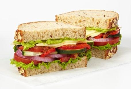 California Veggie Sandwich with smashed avocado, Havarti, red peppers, cucumber, lettuce, red onion, tomatoes, sun-dried tomato spread and balsamic vinaigrette on sliced multigrain