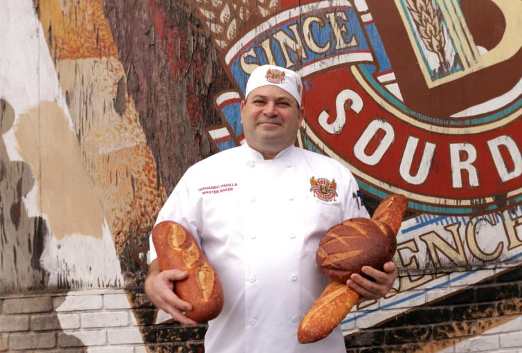 Fernando Padilla outside 10th Avenue Bakery holding bread